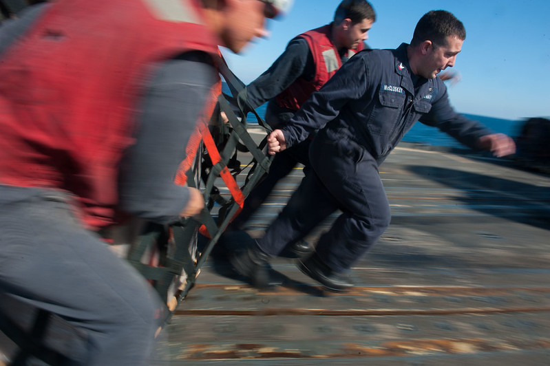 Sailors hurry to slide a pallet of food away from the receiving area of the flight deck