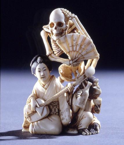 019- Netsuke esqueleto con abanico detrás de la mujer que toca el samisen y un mono que bebe sake-Hecho de marfil-realizado por Gyokkosai -© Trustees of the British