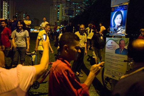 Lee Li Lian's poster illuminated by a flashing light. A lot of pple took turns to snap a picture of her with their mobiles.