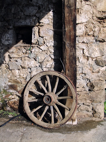 An old wagon wheel leans against a stone barn in a village in the Picos de Europa, Spain