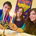 12-065 -- Max Polisky '13, Lizzy Rubel '13 and Dana Chudnovskaya '13 light menorah candles at a Hanukkah celebration.