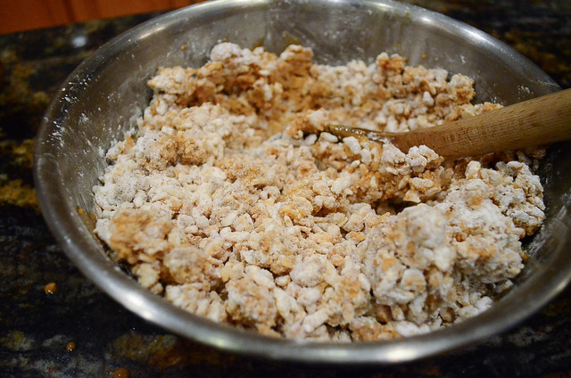 The Rice Krispie mixture being mixed with a wooden spoon.
