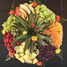 Artfully arranged seasonal fruits including pineapple, green and red grapes, apples, oranges, kiwi, strawberries and honeydew melons.