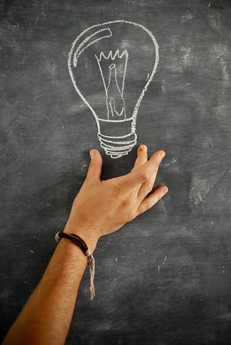 mano che indicata una lampadina disegnata con il gesso sulla lavagna