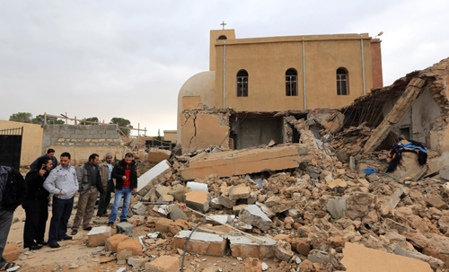 Libyans look at the destroyed side room of the Coptic church on December 31, 2012, damaged following an explosion at night in the Mediterranean town of Dafinya, just west of Misrata in which two Egyptians were killed. by Pan-African News Wire File Photos