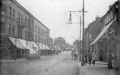 "A black-and-white photo looking down a street with tramlines running along it and a few horse-drawn vehicles visible.  The terrace on the left has canopies over the ground-floor shops and a couple of large signs on the floors above, reading ""J Finer / Tailor"" and ""W E Pratt""."