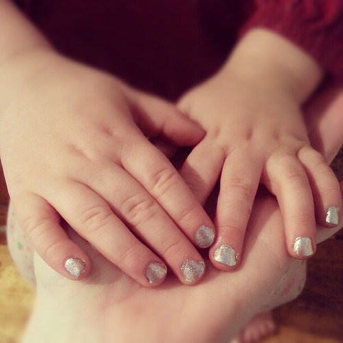 Silver bells Christmas nails on pudgy two year old fingers.