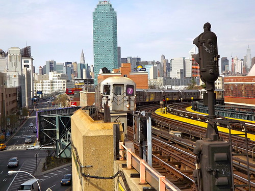 Manhattan in the background, with the 7 train approaching 33 St-Rawson St Station