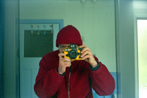 reflected self-portrait with Motormarine II camera and red hat by pho-Tony