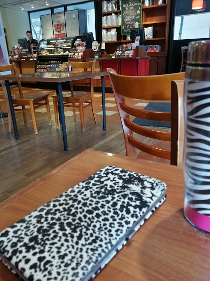 A zebra-striped coffee mug and a leopard-print wallet on a table in a coffee shop