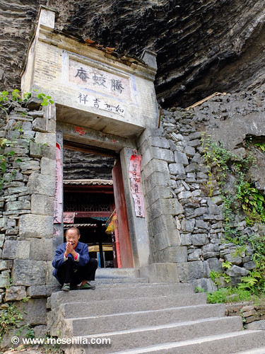 Xinès assegut davant l'entrada del temple budista xinés