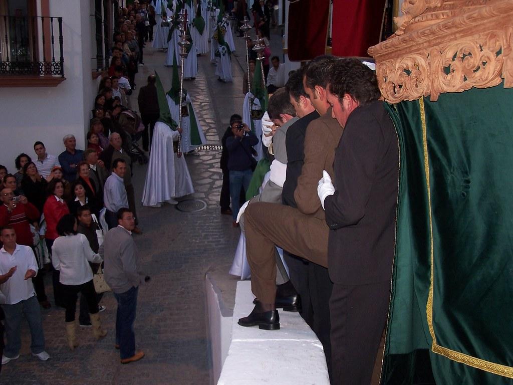 La cuadrilla de Los Blancos da una lección cada año de cómo sacar los tronos por la esquina del Antiguo Ayuntamiento, apoyando incluso una pierna en la albarrá mientras cargan el trono para