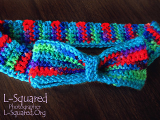 Crocheted bow tie laying on a dark wooden surface. The bow tie is made of yarn that is dyed various colors including green, teal, blue, purple and red.