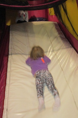 Lucy has her own unique way of doing the slide at the bounce house.