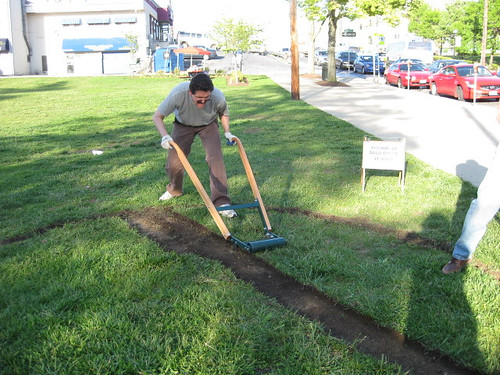 Image of a man removing sod from a lawn. He is preparing the property for conservation landscaping.