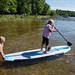 Mom attempts to stand up paddleboard, with a dog