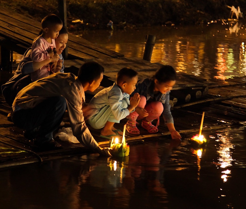 Thai family setting their candle-lit krathongs into the river during Loy Krathong