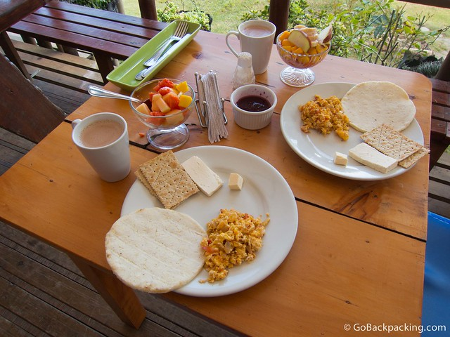 Typical Colombian breakfast: arepas, eggs with onion and tomato, cheese, fruit salad, and coffee or hot chocolate