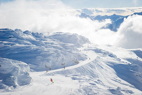Skiing and riding off of Whistler Peak