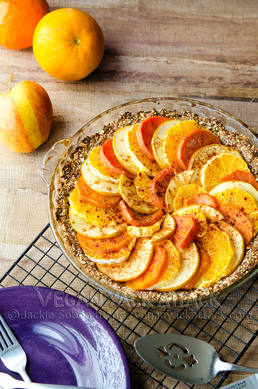 Layered fruit tart with gluten-free crust in a glass pie dish on a cooling rack