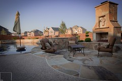 Sunken Outdoor Living Area with Flagstone Fireplace and Decking and A Custom Mantle