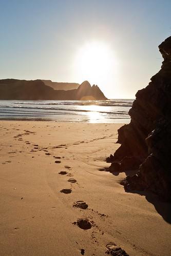 light sea sky sunrise bay three sand rocks cliffs reflected footsteps gower