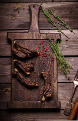 Roasted meat and spices on chopping board. Dark wo…