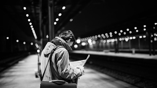 bw reading newspaper blackwhite bokeh citylife streetphotography trainstation wait citynight udine nikond600 50mmafsf14g