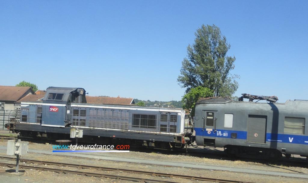 Une locomotive thermique BB 66000 de l'activité INFRA SNCF stationnant avec un wagon graisseur de caténaires