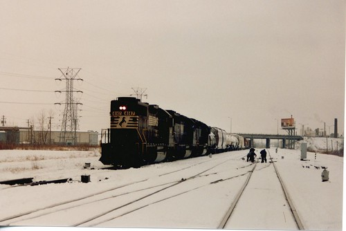Eastbound Norfolk Southern freight train departs the Belt Railway of Chicago's Clearing Yard, passing a snow shoveling track maintenance crew.  Chicago Illinois.  January 1987. by Eddie from Chicago