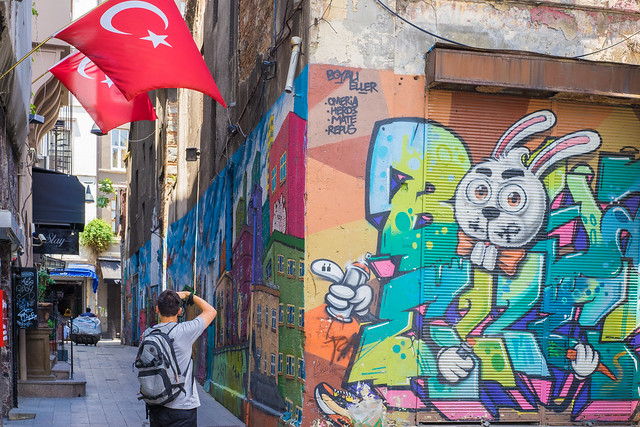 Young Man Taking Photo of Alley full of Graffiti