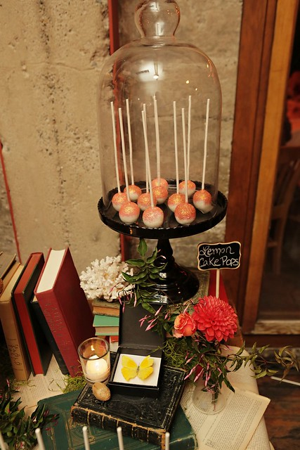Books, florals, coral, and a framed butterfly as props for a literary/biology themed affair!. Cake pops under a glass cloche add a little sparkle!
