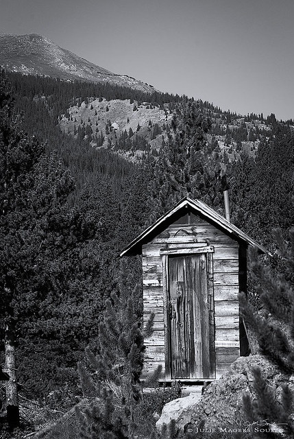 Colorado outhouse photo in black and white, of a primitive rustic privy located in the alpine ghost town of Independence, Colorado.