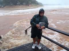 Moneys Creek Bargara. Husband, Len, protects his morning paper while checking out the high water levels.