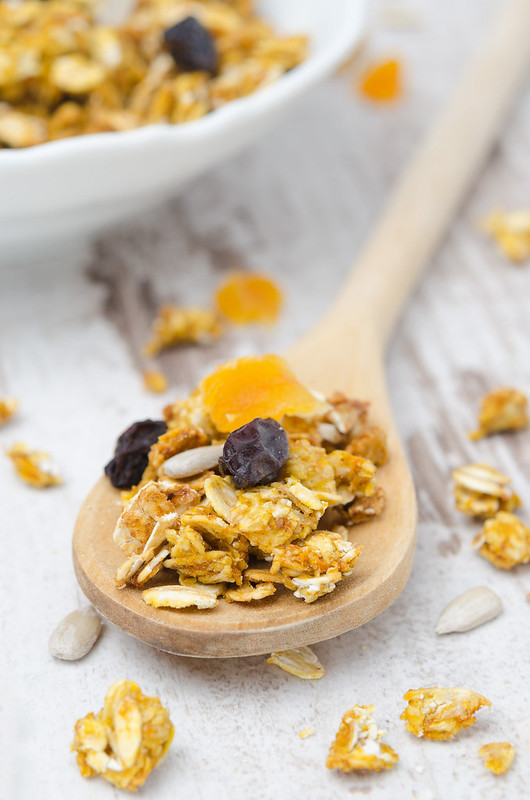 pumpkin granola with dried fruit and seeds in a spoon closeup