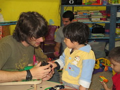Colt Duttweiler interacts with a small child in the nursery at the La Limonada school