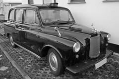 compact car(0.0), automobile(1.0), vehicle(1.0), austin fx4(1.0), mid-size car(1.0), antique car(1.0), sedan(1.0), vintage car(1.0), land vehicle(1.0), luxury vehicle(1.0),