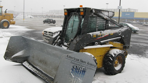 A little skid steer tractor with a huge snowplow attatchment.  Niles Illinois.  Tuesday, March 5th, 2013. by Eddie from Chicago