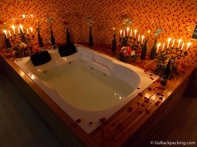 Candlelit jacuzzi with flowers and a bottle of wine