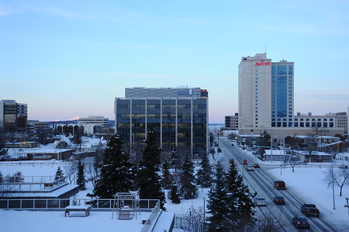 "Clear winter day, pink Mt Denali in the distance, Nana Corporation building, Marriott hotel, cars on ""I"" Street, snow, trees on the Parkstrip, downtown Anchorage, Alaska, USA by Wonderlane"