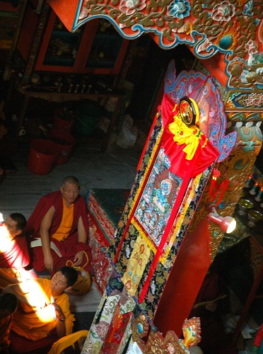 Lama Jampa under a thangka, a beam of light coming in from above, silk decorations, Sakya Lamdre, Tharlam Monastery of Tibetan Buddhism, Boudha, Kathmandu, Nepal by Wonderlane