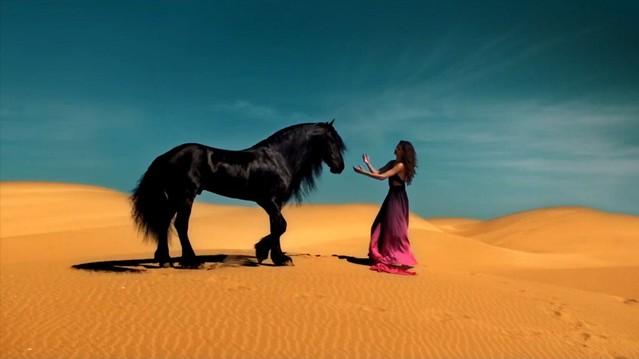 Caballo negro y mujer en el desierto