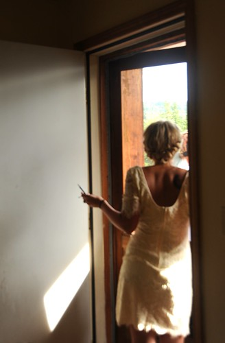 Jessie gets prepared for her wedding, watching guest arrive, wearing her day frock, cabin door, Fairbanks, Alaska, USA by Wonderlane