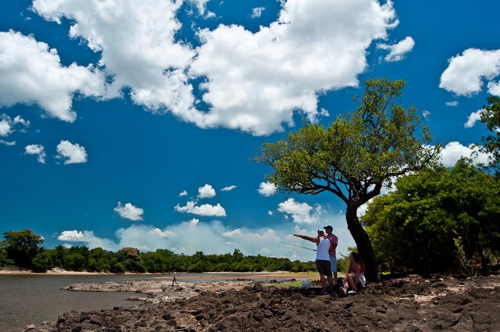 """Un grupo de amigos se refugian en la sombra de un árbol mientras visitaban la orilla del río Tebicuary para pescar y compartir """"Tereré"""" en el pasado mes de Febrero. En dicha temporada se pudo evidenciar una llamativa baja del nivel del río que para la actividad de pesca no presentó ningún inconveniente. (Elton Núñez)"""