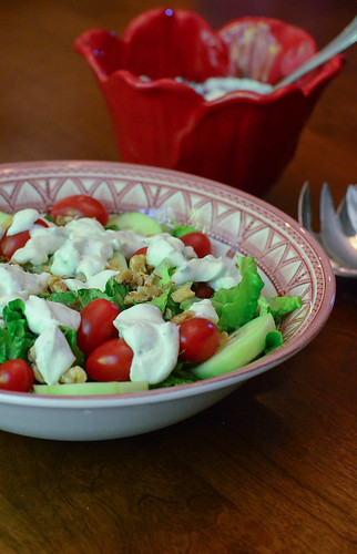 A dish of Light and Creamy Blue Cheese Dressing with some served on top of a salad.