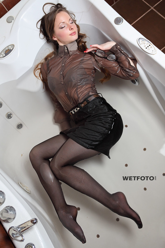 #248 Wetlook in Business Clothes with Sexy Girl. Beautiful brunette in shirt and black skirt with tights in heels, get wet fully clothed in the jacuzzi and shower.