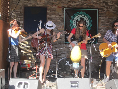 Four female musicians playing their guitars and fiddles.