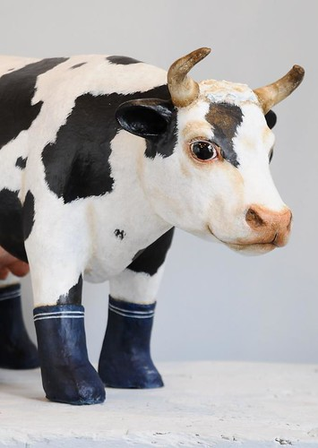 paper mache cow wearing boots