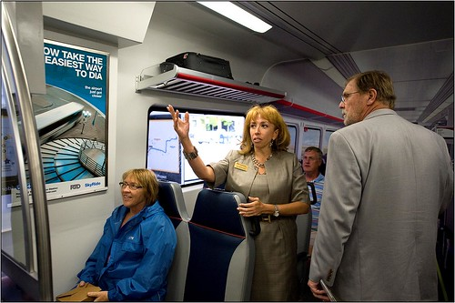 Photo of RTD Public Information Specialist Ana Mostaccero providing details of interior design on commuter rail car mock up