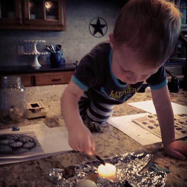 "Owen ""helping"" make Ukrainian eggs. Yes, that's a candle.  Don't worry, mom is close by!"